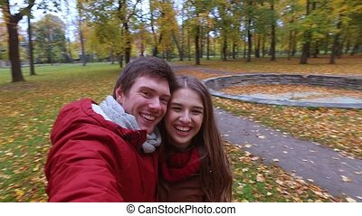 happy couple recording video in autumn park - love,...