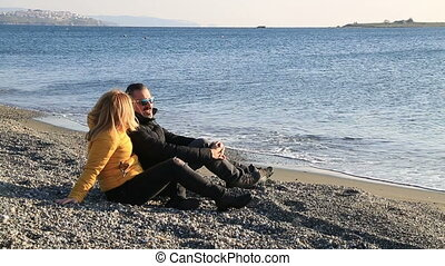 Happy couple relaxing at the winter beach