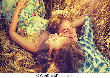 Happy couple relaxing outdoors on wheat field, love concept