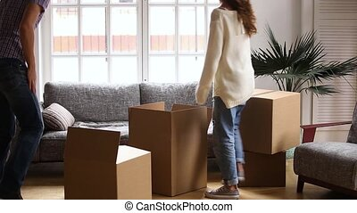 Happy couple relaxing with cardboard boxes moving in new...