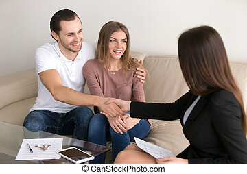 Happy couple renters owners shaking hands with real estate...