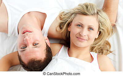 Happy couple resting in bed