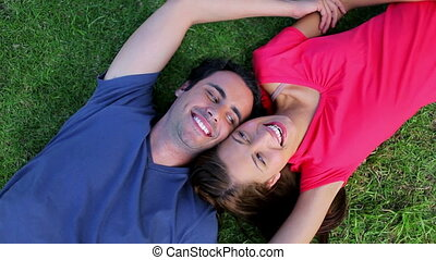 Happy couple resting while lying on the grass in a parkland