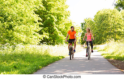 happy couple riding bicycle outdoors - fitness, sport,...