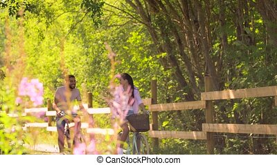happy couple riding bicycles at summer park