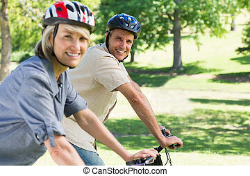 Happy couple riding bicycles in par