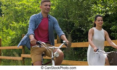 happy couple riding fixed gear bicycles in summer
