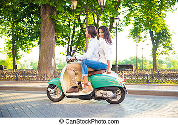 Happy couple riding on a scooter