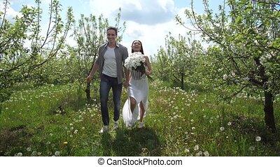 Happy couple running holding hands in fruit garden