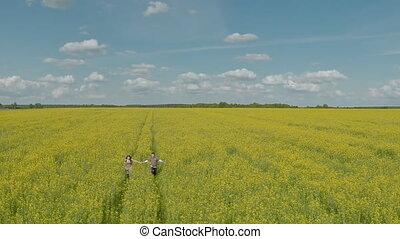 Happy couple running in rape field