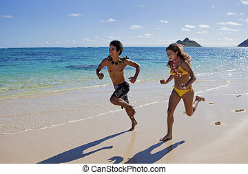 happy couple running on a hawaii beach