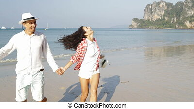 Happy Couple Running On Beach Holding Hands Young Happy Man...