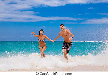 happy couple running on the beach