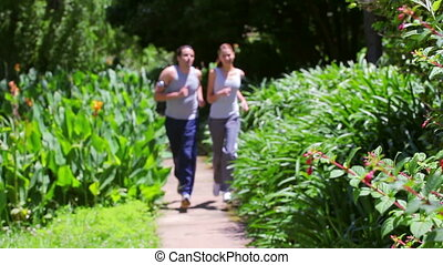 Happy couple running together in a parkland
