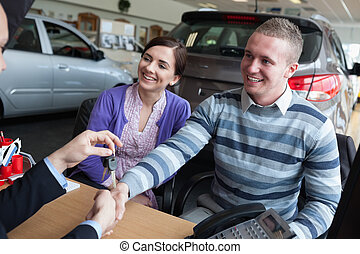 Happy couple shaking the hand of a salesman