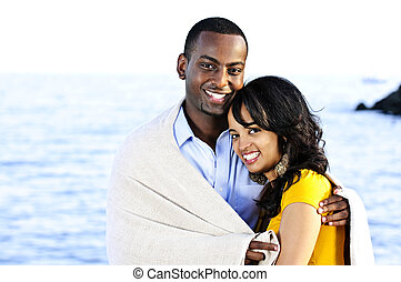 Happy couple sharing blanket - Young romantic sharing a...