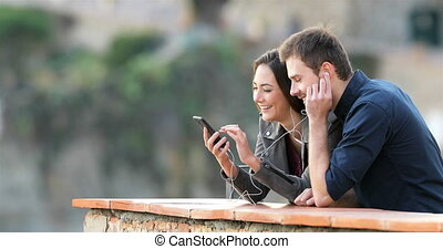 Happy couple sharing music from smart phone in a balcony -...