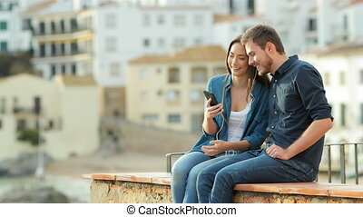 Happy couple sharing music on a ledge at sunset - Happy...
