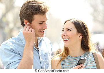Happy couple sharing online music in the street