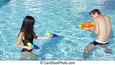 Happy couple shooting off water guns in pool - Happy young...