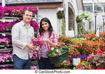 Happy couple shopping for flowers