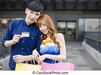 happy couple showing credit card in front of shopping mall