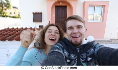 Happy couple showing keys of their new house