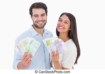 Happy couple showing their money on white background