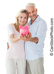 Happy couple showing their piggy bank on white background
