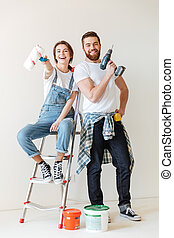 Happy couple showing tools for repair while standing near ladder