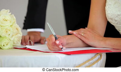 Happy couple signing their wedding register smiling at...