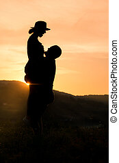 Happy couple silhouette with romantic sunset background