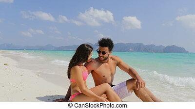 Happy couple Sit On Beautiful Beach Talking, Man And Woman...
