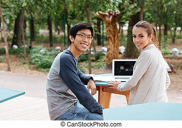 Happy couple sitting and using laptop together