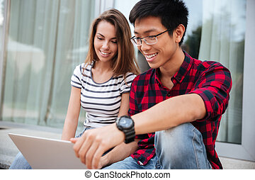 Happy couple sitting and using laptop together outdoors
