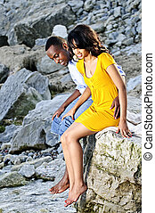 Happy couple sitting at rocky shore - Happy couple dipping...