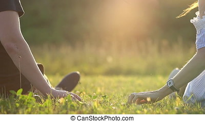 happy couple sitting in a field and watching the sunset