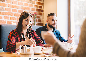 Happy couple sitting in a restaurant, eating