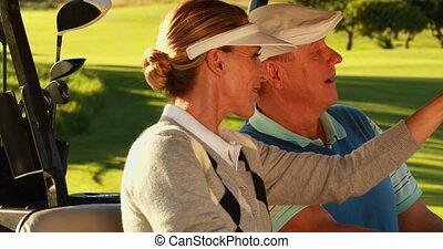 Happy couple sitting in kart lookin