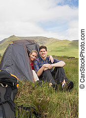 Happy couple sitting in their tent after a hike and looking...