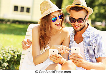 Happy couple sitting on a bench with smartphones