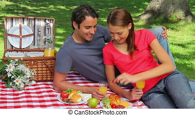 Happy couple sitting on a blanket during a picinic