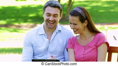 Happy couple sitting on a park bench using tablet