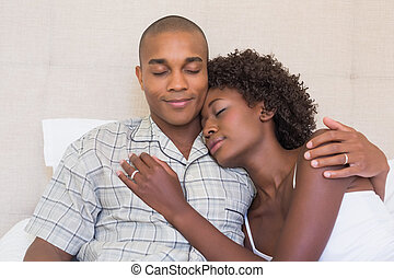 Happy couple sitting on bed cuddling at home in the bedroom