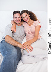 Happy couple sitting on bed