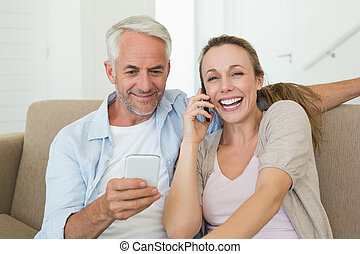 Happy couple sitting on couch talking and texting on their phones at home in the living room