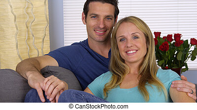 Happy couple sitting on couch together