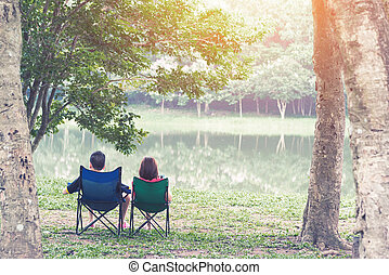 Happy couple sitting on deck chairs in mountain with lake. Family, old age, travel, tourism and people concept. Vacation relax time in nature with sunlight.