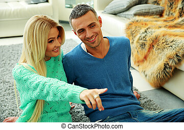 Happy couple sitting on floor at home