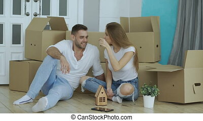 Happy couple sitting on floor in new house. Young man give keys to his girlfriend and kissing her